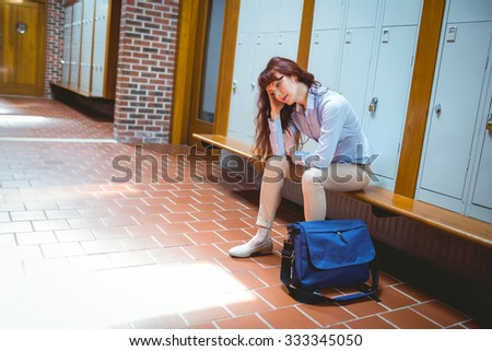 Mature student feeling stressed in hallway at the university - stock photo