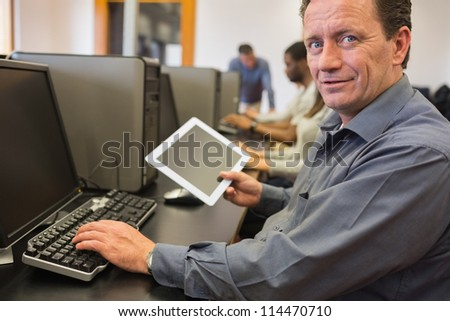 Mature student holding tablet pc in computer class - stock photo