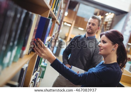 Mature student removing book from shelf in college library