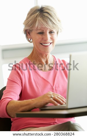 Mature student using computer in class - stock photo