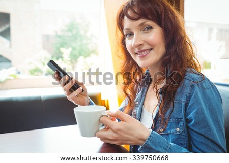 Mature student using phone in cafe at the university