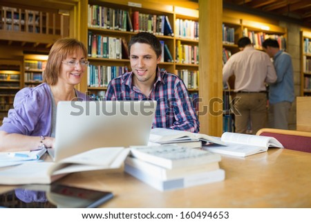 Mature students using laptop while two men at bookshelf in the library