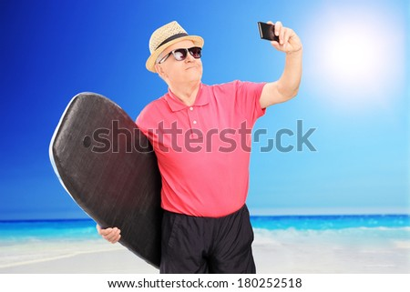 Mature surfer taking a picture of himself with cell phone at the beach - stock photo