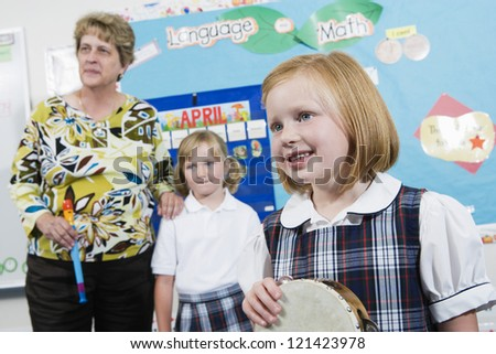 Mature teacher with female students in music class - stock photo