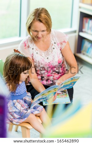 Mature teacher with schoolgirl reading book in library - stock photo