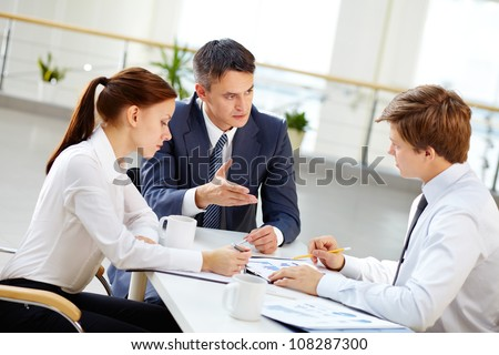 Mature team leader motivate young employee by gesture to share his business ideas - stock photo