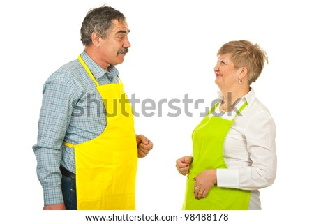Mature team of chefs in yellow and green aprons having conversation isolated on white background - stock photo
