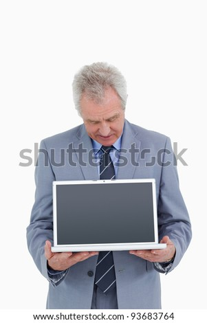 Mature tradesman holding and looking at laptop screen against a white background