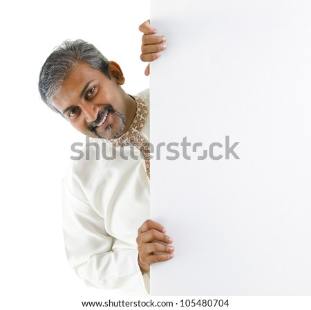 Mature traditional Indian male hiding on a blank space. - stock photo