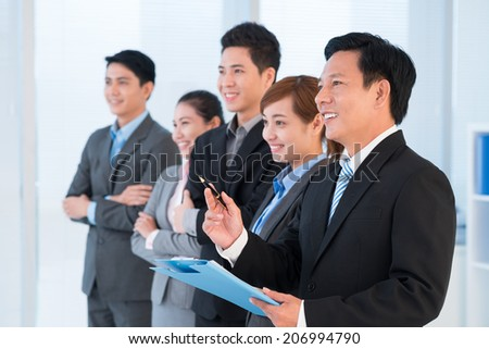 Mature Vietnamese businessman conducting presentation for colleagues, side view - stock photo