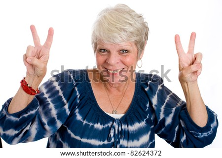 Mature, white haired woman smiling and giving a peace sign with her two hands. - stock photo
