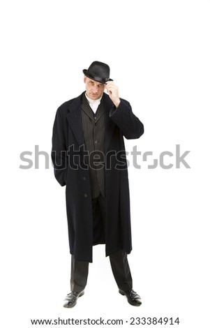 Mature white male dressed in a sharp black and white suit wearing a bowler hat and waistcoat standing with one hand in his pocket and one on his hat casually - stock photo