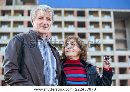 Mature wife with house key in hand looking at smiling husband - stock photo