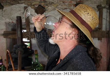 Mature winemaker testing wine in old winery - stock photo