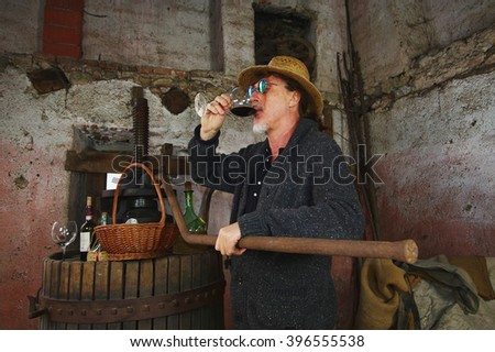 Mature winemaker testing wine in old winery