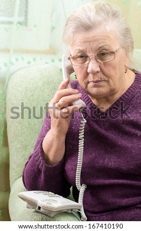 Mature woman age 70-75 years speaking on the phone. - stock photo