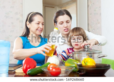 Mature woman and adult daughter with child cook vegetables  and oil in kitchen at home