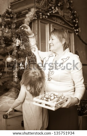Mature woman  and child preparing for  Christmas at home. Imitation of an old photo