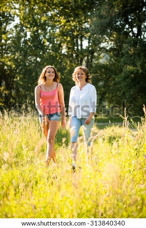 Mature woman and her teenage daughter walking together outdoor in nature on sunny summer day