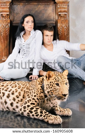 Mature woman and young man near to spotty leopard, on studio. - stock photo