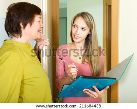 mature woman answer questions of smiling woman with papers at door in home  - stock photo
