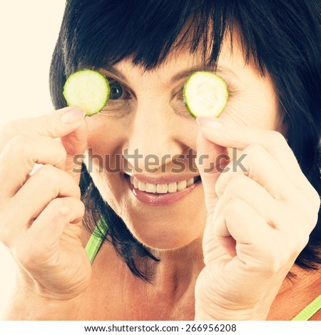 Mature woman beauty portrait. Woman holding slices of cucumber. Beauty treatment - stock photo