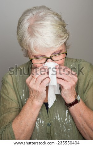 mature woman blowing her nose - stock photo