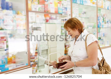 Mature woman buys drugs at the pharmacy - stock photo