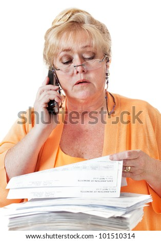 Mature woman calling to discuss healthcare benefit paperwork - stock photo