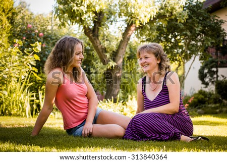 Mature woman chatting with her teenage daughter outdoor in nature - stock photo
