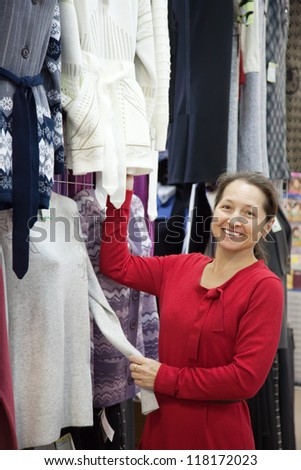 Mature woman  chooses clothes at fashionable shop