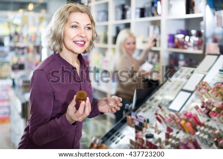 mature woman choosing face powder on display and smiling