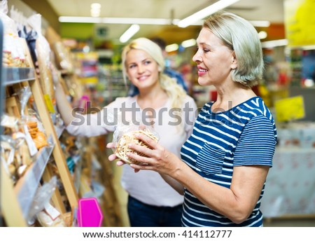 Mature woman choosing pastry in the bakery section of the supermarket