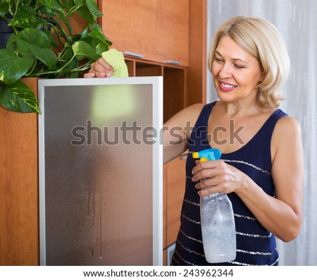 Mature woman cleaning glass door of furniture