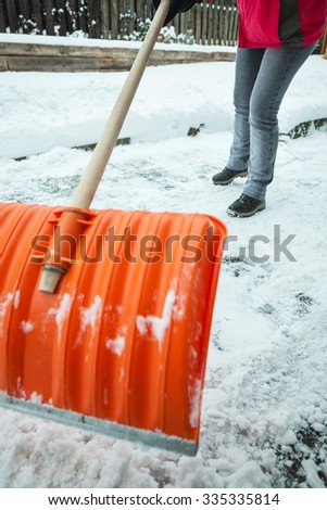 Mature woman cleaning snow in front of her house. Selective focus on background. - stock photo