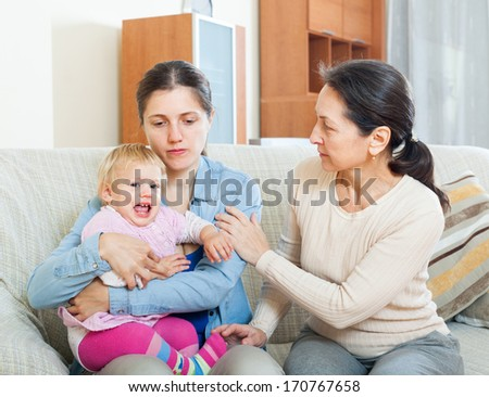 Mature woman comforting  daughter with baby at home