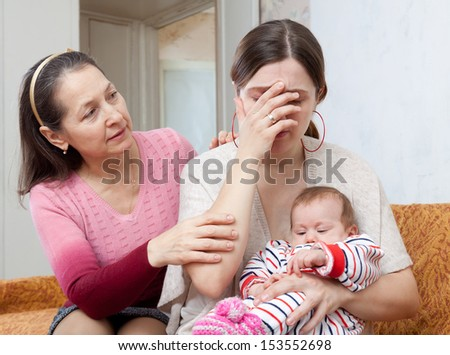 Mature woman comforts crying adult daughter with baby at home - stock photo