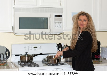 mature woman cooking in the kitchen by the stove - stock photo