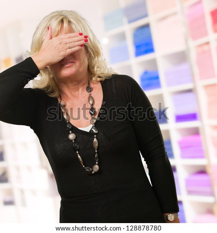Mature Woman Covering Her Eyes at a clothes shop - stock photo