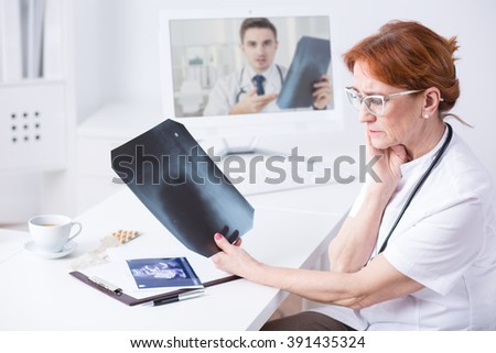 Mature woman doctor analysing x-ray picture during medical consultation with another doctor via internet