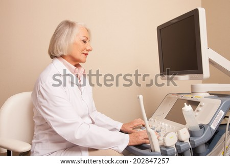 Mature woman doctor checking ultrasound machine before patient checkup.