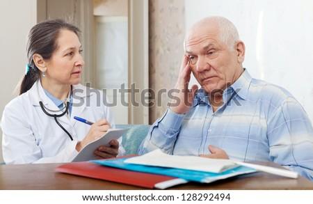 Mature woman doctor examining the senior patient - stock photo