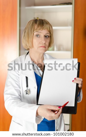 Mature woman doctor holding and showing blank clipboard with space for text - stock photo
