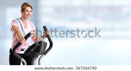 Mature woman doing exercise on elliptical trainer. - stock photo