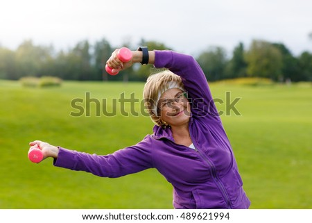 Mature woman doing exercises with dumbells at park in evening