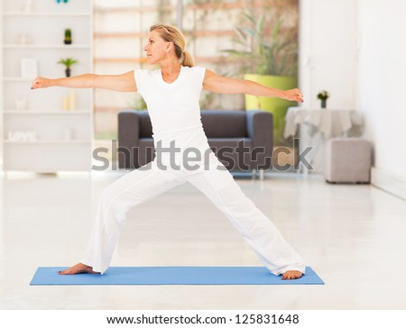 mature woman doing fitness exercise at home - stock photo