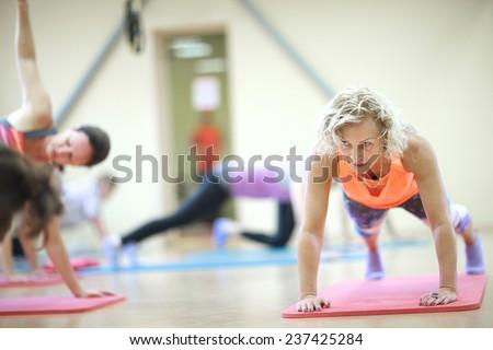 Mature woman doing push-up on padded mat - stock photo