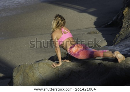 Mature woman doing yoga at the beach/Morning Yoga/Woman doing her yoga at the beach during the early morning - stock photo