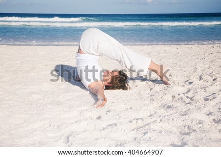 Mature woman doing yoga on the beach