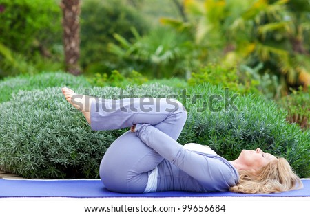 mature woman doing yoga position outside in the garden - stock photo